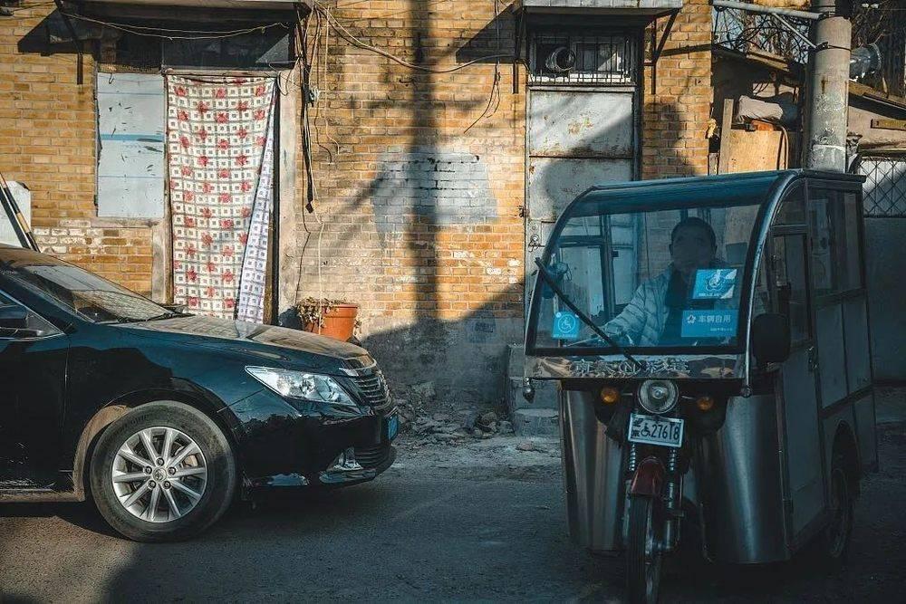 2019年3月15日,北京,汽车和破旧的代步车,在胡同里并存